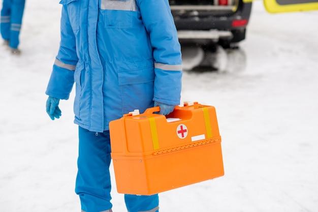 Junger sanitäter in blauer arbeitskleidung mit erste-hilfe-kasten, während er zu einer kranken person geht, nachdem er aus dem krankenwagen ausgestiegen ist
