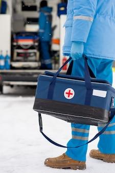 Junger sanitäter in blauer arbeitskleidung und medizinischen handschuhen mit erste-hilfe-kasten, während er nicht weit vom krankenwagen entfernt steht