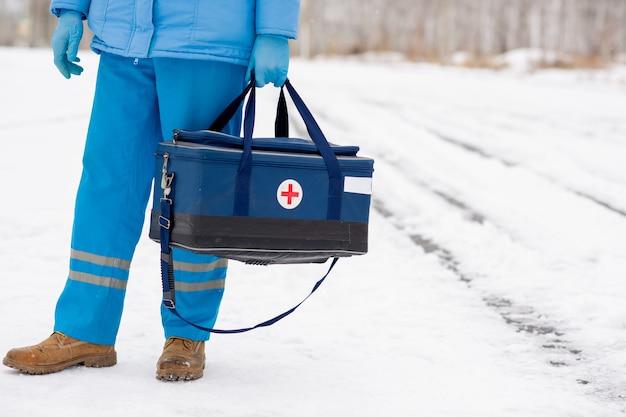 Junger sanitäter in der blauen arbeitskleidung, die erste-hilfe-satz mit rotem kreuz hält, während er am wintertag auf schnee steht