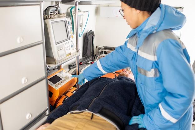 Junger sanitäter in einheitlichem druckknopf auf medizinischer erste-hilfe-ausrüstung, während er durch bewusstlosen mann auf trage steht