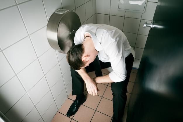 Junger schlafender betrunkener mann auf der toilette