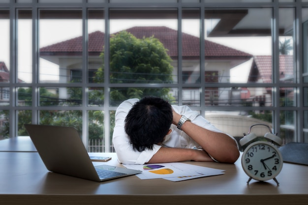 Junger schlafender geschäftsmann und nahe laptop im büro überarbeitet.