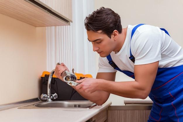 Junger schlosser, der an der küche arbeitet