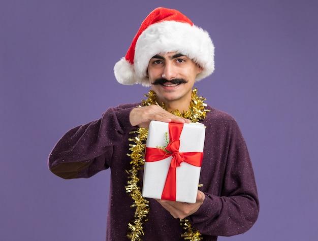 Junger schnurrbärtiger mann mit weihnachtsmütze mit lametta um den hals, der weihnachtsgeschenk mit glücklichem gesicht lächelnd über lila wand hält