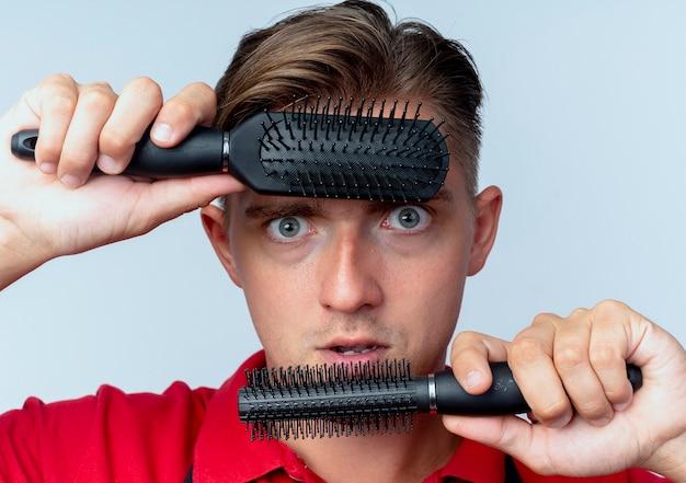 Junger schockierter blonder männlicher friseur in uniform hält haarkämme auf stirn und kinn, die kamera betrachten