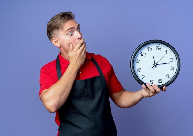 Junger schockierter blonder männlicher friseur in uniform hält und schaut auf uhr isoliert auf violettem raum mit kopierraum