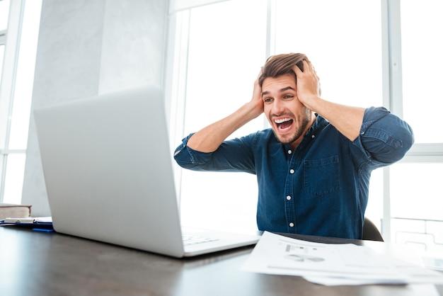 Junger schockierter junger mann gekleidet im blauen hemd, während er seinen kopf mit den händen hält und laptop betrachtet
