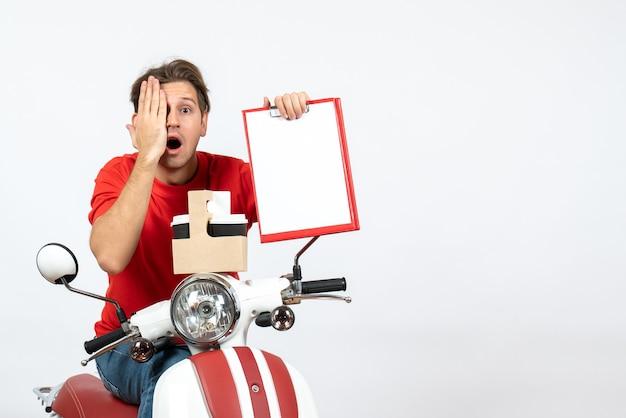 Junger schockierter kuriermann in roter uniform, der auf roller sitzt und befehle und dokumente hält, die sein auge auf gelber wand schließen