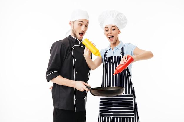 Junger schockierter mannkoch in der schwarzen uniform, die pfanne in händen hält, während frau in gestreifter schürze unter verwendung von flaschen ketchup und senf darauf kocht