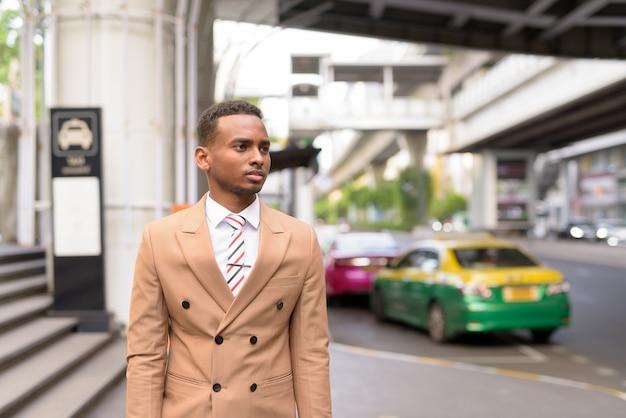Junger schöner afrikanischer geschäftsmann, der auf taxi in der stadt wartet