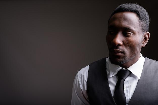 Junger schöner afrikanischer geschäftsmann gegen grauen hintergrund