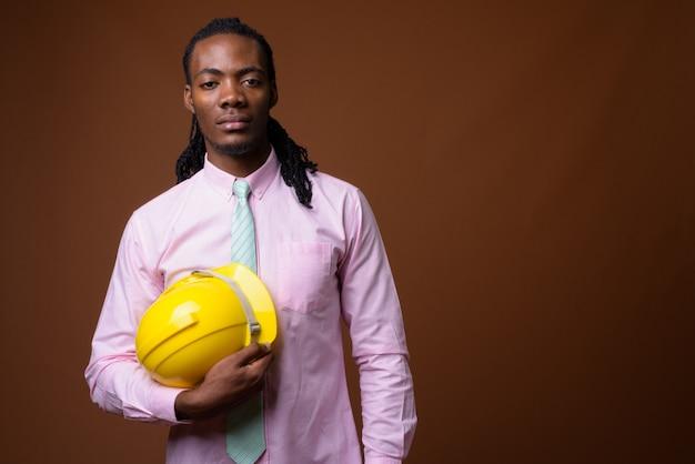 Junger schöner afrikanischer geschäftsmann mit helm vor braunem hintergrund