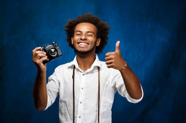 Junger schöner afrikanischer mann, der alte kamera über blauer wand hält.