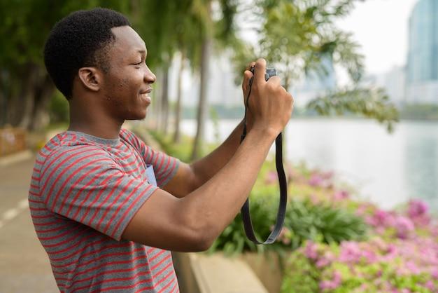 Junger schöner afrikanischer mann, der bilder mit kamera im park nimmt