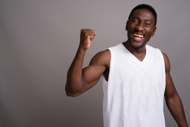 Junger schöner afrikanischer mann gegen grauen hintergrund