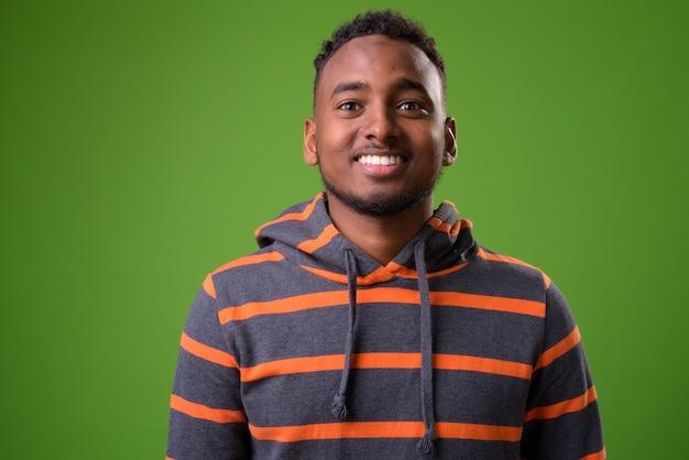 Junger schöner afrikanischer mann gegen grünen hintergrund