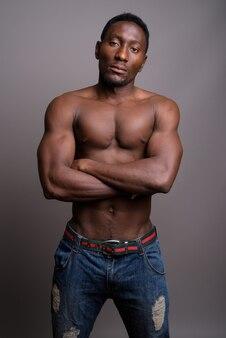 Junger schöner afrikanischer mann hemdlos gegen grauen hintergrund