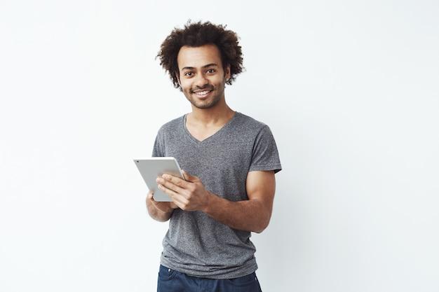 Junger schöner afrikanischer mann lächelnd, der silberne tablette hält und spiele spielt oder eine buchungs-app gegen weiße wand verwendet.