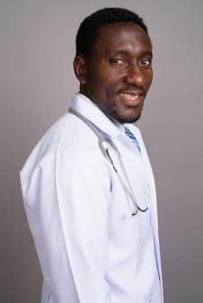 Junger schöner afrikanischer mannarzt gegen grauen hintergrund