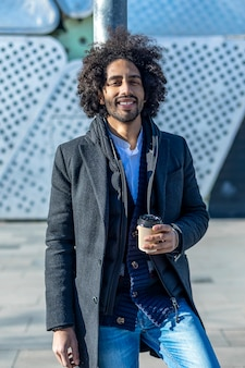 Junger schöner afroamerikanermann, der glücklich lächelt. stehend mit einem lächeln im gesicht, das eine tasse kaffee zum mitnehmen in der stadtstraße trinkt.
