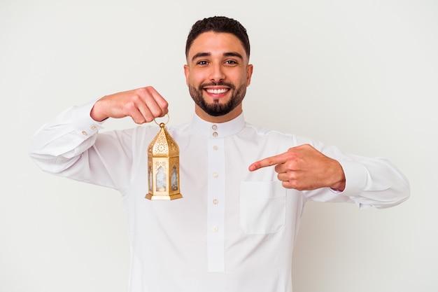 Junger schöner arabischer mann, der eine lampe hält