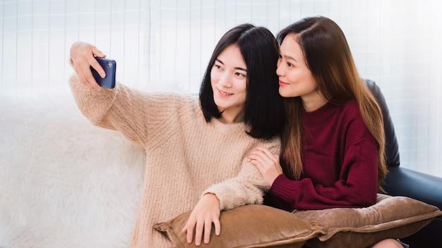 Junger schöner asiatischer lesbischer paarliebhaber, der smartphone selfie zusammen im wohnzimmer zu hause mit lächelndem gesicht verwendet. konzept der lgbt-sexualität mit glücklichem lebensstil zusammen.