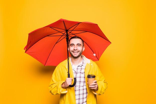 Junger schöner bärtiger mann im gelben regenmantel mit dem roten regenschirmtrinkkaffee lokalisiert über orange hintergrund
