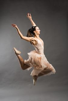 Junger schöner balletttänzer im beige badeanzug, der auf punkten auf hellgrauem studiohintergrund aufwirft