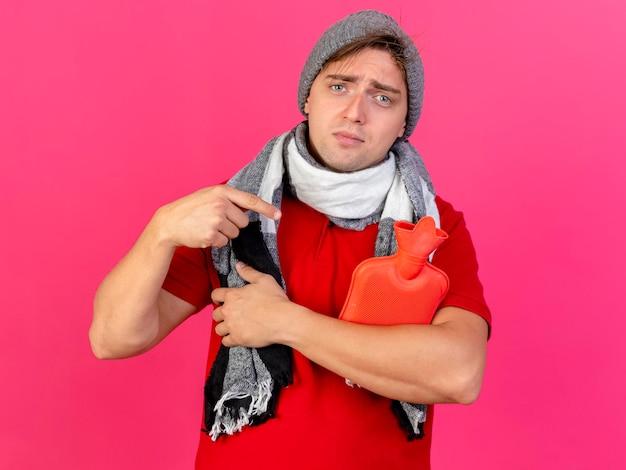 Junger schöner blonder kranker mann, der wintermütze und schal hält und auf wärmflasche zeigt, die front lokalisiert auf rosa wand mit kopienraum betrachtet