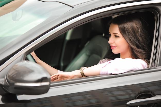 Junger schöner brunette innerhalb des schwarzen autos.