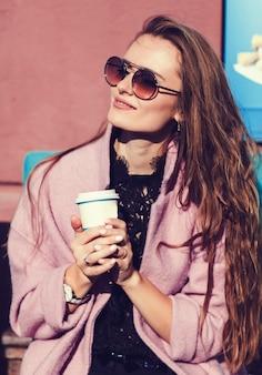 Junger schöner brunette mit kaffee in der stadt