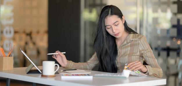 Junger schöner designer, der an ihrem projekt mit digitaler tablette arbeitet