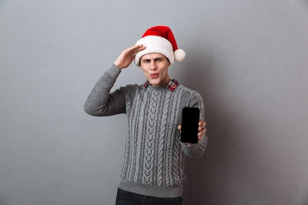Junger schöner emotionaler mann, der weihnachtsweihnachtsmütze trägt