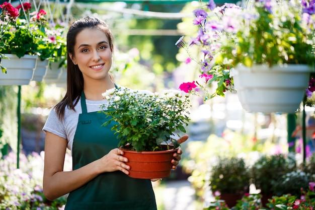 Junger schöner florist, der unter blumen lächelt.