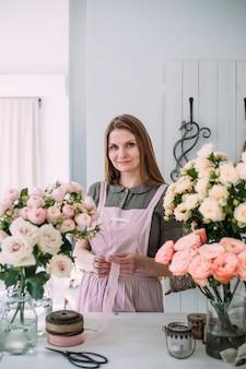 Junger schöner florist in einem blumenladen