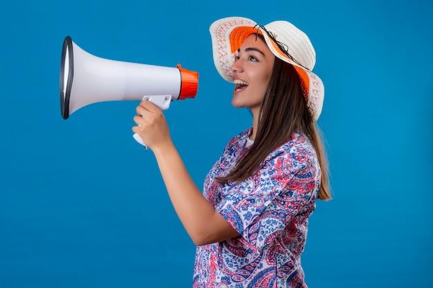 Junger schöner frauentourist im sommerhut, der zu megaphon mit glücklichem gesicht steht, das über lokalisiertem blauem hintergrund steht