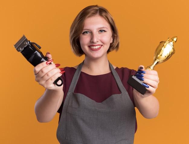 Junger schöner friseur der frau in der schürze, die trimmermaschine und goldtrophäe hält, die front glücklich und positiv lächelnd über orange wand steht