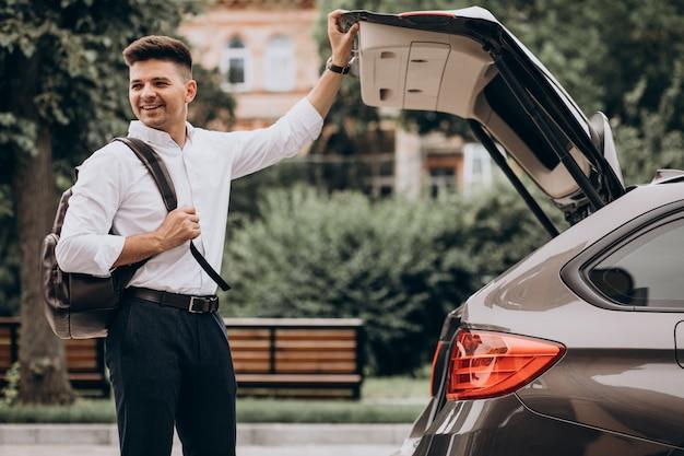 Junger schöner geschäftsmann, der durch auto mit reisetasche steht