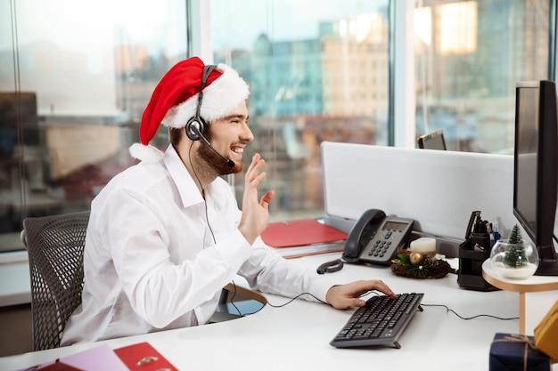 Junger schöner geschäftsmann, der im büro am weihnachtstag arbeitet.