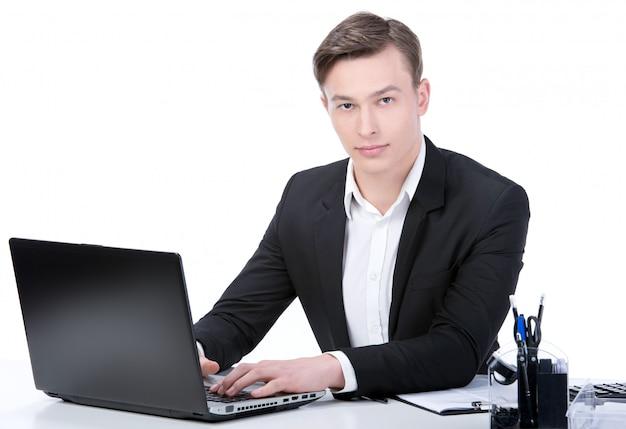 Junger schöner geschäftsmann, der im büro arbeitet.