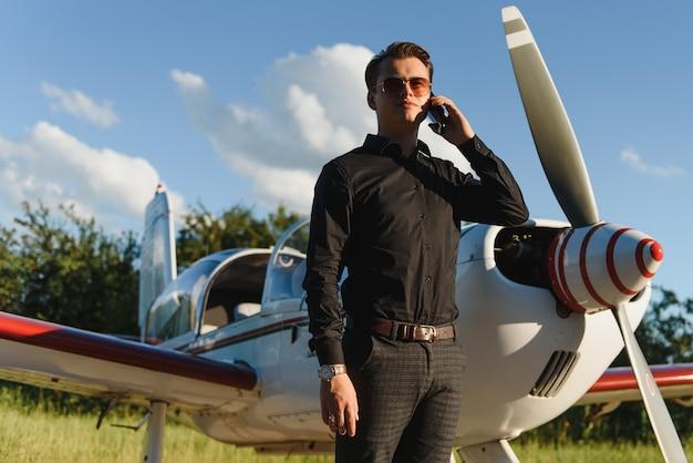 Junger schöner geschäftsmann, der nahe privatflugzeug steht