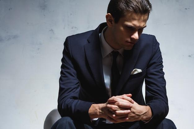 Junger schöner geschäftsmann im schwarzen anzug sitzt im stuhl auf grauer wand