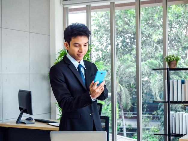 Junger schöner geschäftsmann in anzug und krawatte stehend, während er blaues mobiltelefon nahe schreibtisch mit laptop-computer, bücherregal und glasfenster im büro mit natürlichem grünem baum verwendet.