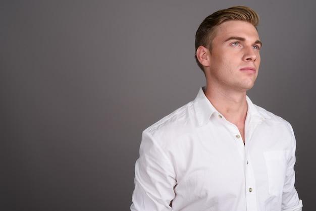 Junger schöner geschäftsmann mit blondem haar auf grauer wand