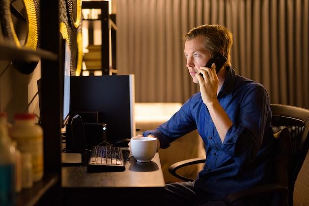 Junger schöner geschäftsmann mit kaffee, der am telefon spricht, während von zu hause aus gearbeitet wird