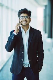 Junger schöner indischer geschäftsmann, der auf handy in modernem büro spricht