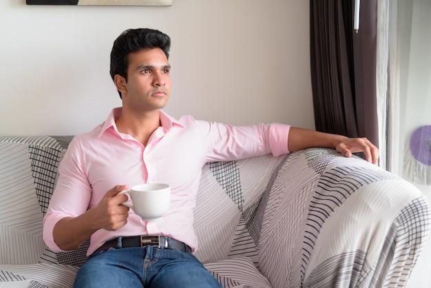Junger schöner indischer geschäftsmann, der beim kaffeetrinken im wohnzimmer denkt