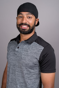 Junger schöner indischer mann, der auf grauem hintergrund lächelt