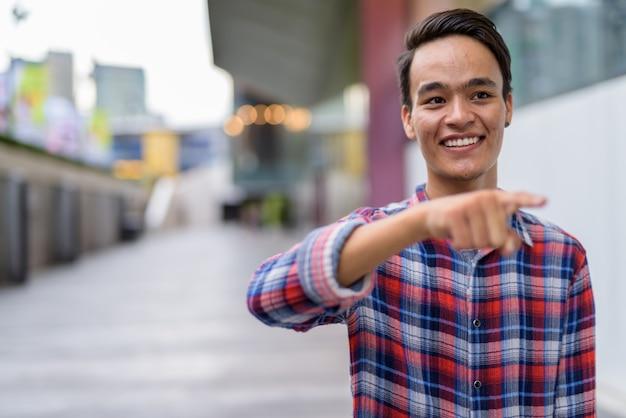 Junger schöner indischer mann, der die stadt bangkok, thailand erkundet