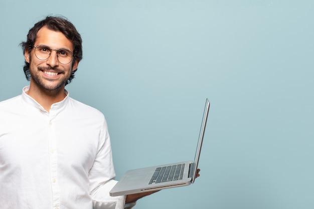Junger schöner indischer mann, der einen laptop hält. business- oder social-media-konzept